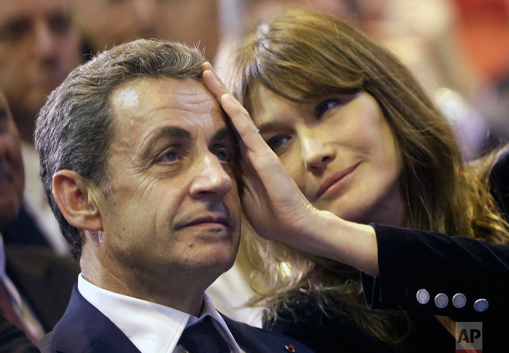 In this Thursday, Oct. 27, 2016 photo, Carla Sarkozy, right, caresses the brow of her husband, the former French President and candidate for France's conservative presidential primary, Nicolas Sarkozy, during a campaign meeting in Marseille, southern France. (AP Photo/Claude Paris)