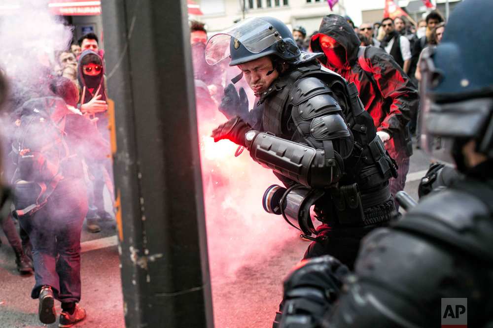 In this Thursday, April 28, 2016 photo, a policeman reacts during a clash with protestors during a protest against the proposed changes to France's working week and layoff practices, in Lyon, central France. French protesters are back on the streets over proposed reforms to the country's labor rules and strikers have forced cancellations and delays at two airports serving Paris. (AP Photo/Laurent Cipriani)