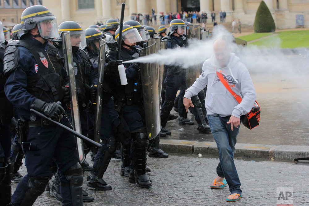 In this Thursday, May 12, 2016 photo, French riot police officers spray pepper gas at a demonstrator during a protest against Labor Law as the Socialist government decided to force the bill through Parliament without a vote, in Paris. France's government is facing a major test as lawmakers hold a no-confidence vote, prompted by a deeply divisive labor law allowing longer workdays and easier layoffs. (AP Photo/Christophe Ena)