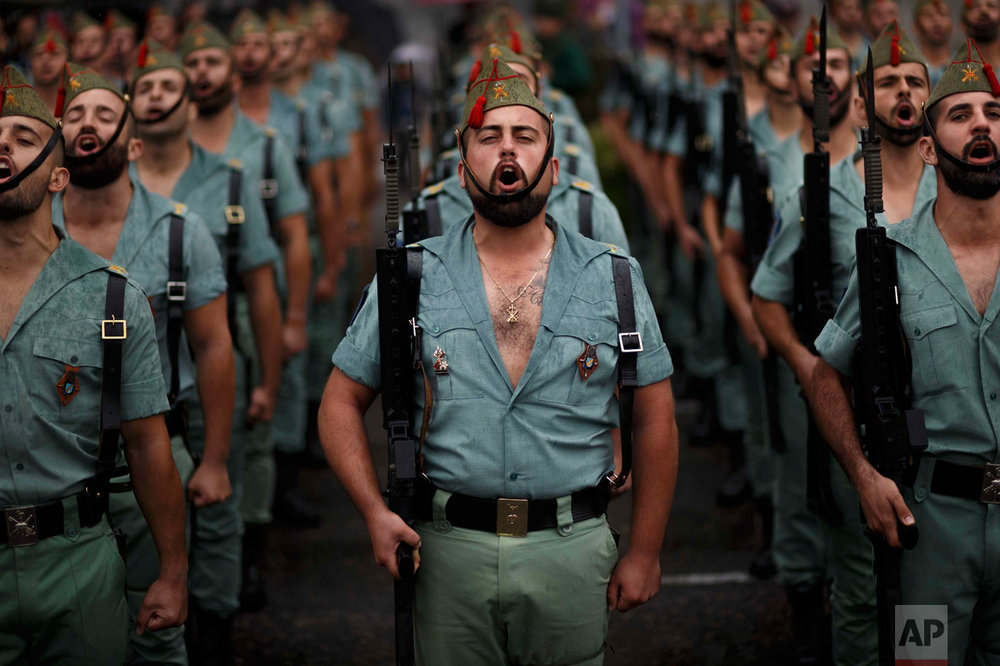 In this Wednesday, Oct. 12, 2016 photo, members of La Legion, an elite unit of the Spanish Army, sing during a military parade as they celebrate a holiday known as 'Dia de la Hispanidad' or Hispanic Day in Madrid. Almost a year into Spain's political deadlock, the country is celebrating its National Day with a military parade of over 3,000 soldiers marching through Madrid and aircraft drawing trails of red and yellow smoke in the sky to represent the flag. (AP Photo/Daniel Ochoa de Olza)