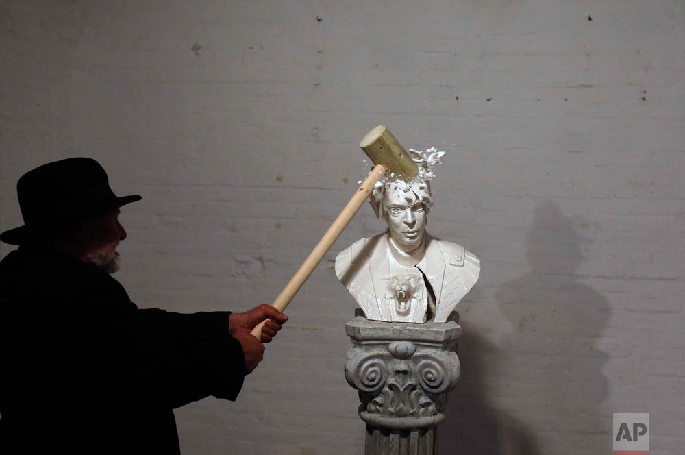 In this Friday, April 22, 2016 photo, Serbian artist Zivko Grozdanic smashes a statue of Prime Minister Aleksandar Vucic in the village of Veliko Srediste, Serbia. The provocative performance took place just one day before Sunday's early election when Vucic and his populist Progressive Party are expected to tighten an already firm grip on power. (AP Photo/Darko Vojinovic)
