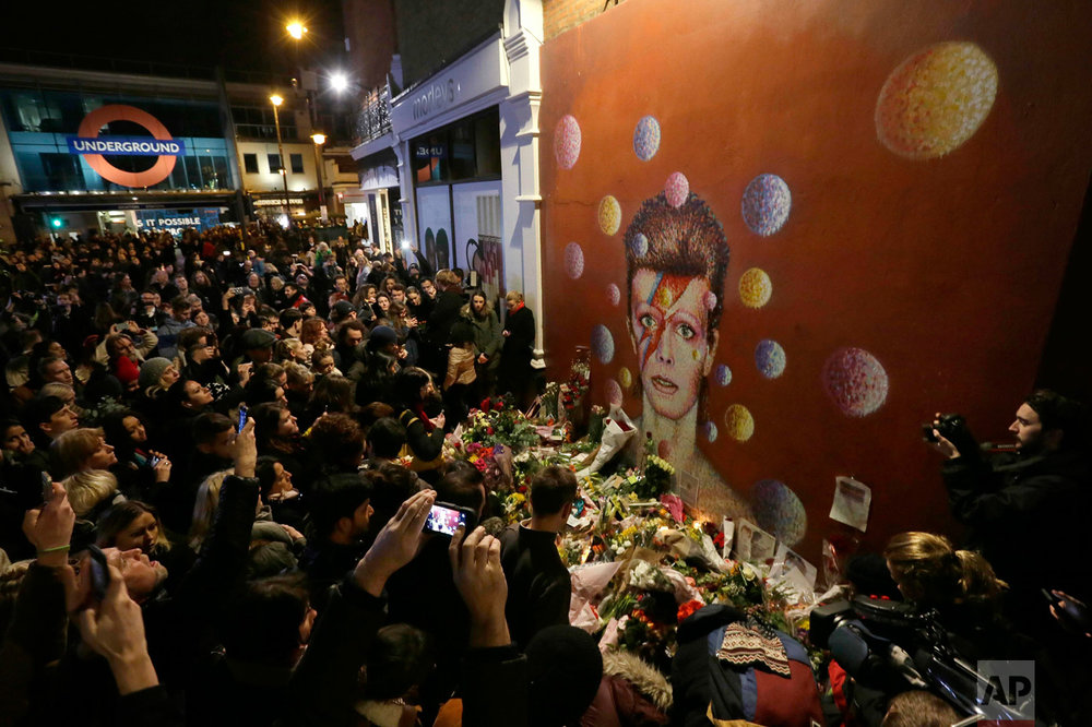 In this Monday, Jan. 11, 2016 photo, people gather next to tributes placed near a mural of British singer David Bowie by artist Jimmy C, in Brixton, south London. Bowie, the other-worldly musician who broke pop and rock boundaries with his creative musicianship, nonconformity, striking visuals and a genre-spanning persona he christened Ziggy Stardust, died of cancer Sunday aged 69. He was born in Brixton. (AP Photo/Tim Ireland)