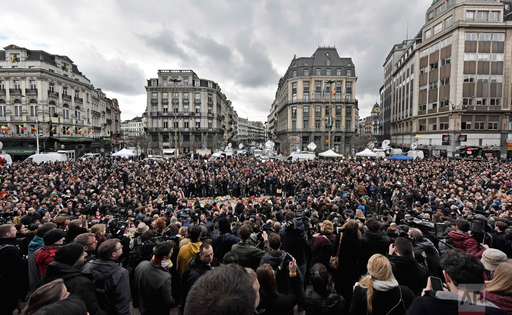 In this Wednesday, March 23, 2016 photo, people observe a minute of silence at the Place de la Bourse in the center of Brussels. Bombs exploded yesterday at the Brussels airport and one of the city's metro stations Tuesday, killing and wounding scores of people, as a European capital was again locked down amid heightened security threats. (AP Photo/Martin Meissner)