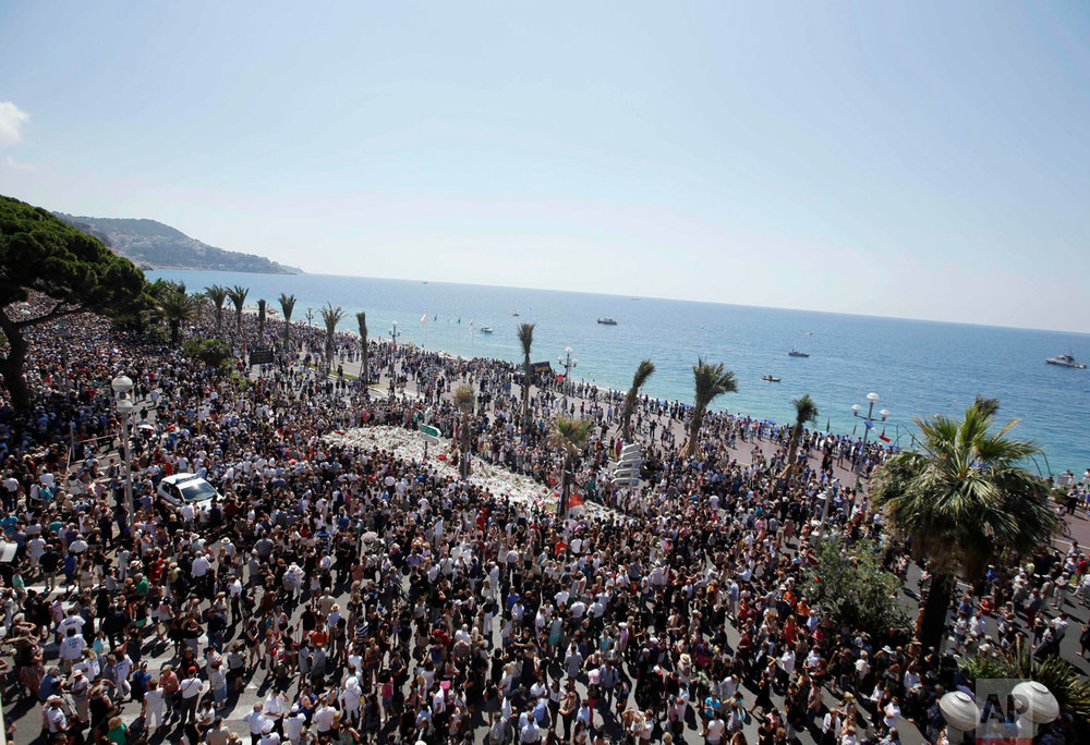In this Monday, July 18, 2016 photo, people gather at a makeshift memorial to observe a minute of silence to honor the victims of an attack near the area where a truck mowed through revelers on the famed Promenade des Anglais in Nice, southern France. France is holding a national moment of silence for 84 people killed by a truck rampage in Nice, and thousands of people are massed on the waterfront promenade where Bastille Day celebrations became a killing field.(AP Photo/Luca Bruno)