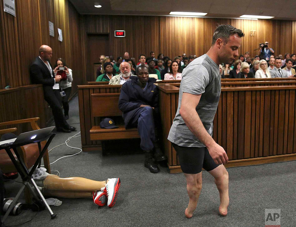 Oscar Pistorius' prosthetics lie on the floor as he walks on his amputated legs during argument in mitigation of sentence by his defense attorney Barry Roux in the High Court in Pretoria, South Africa, on June 15, 2016. An appeals court found Pistorius guilty of murder and not a lesser charge of culpable homicide for the shooting death of his girlfriend Reeva Steenkamp. (Siphiwe Sibeko via AP, Pool)