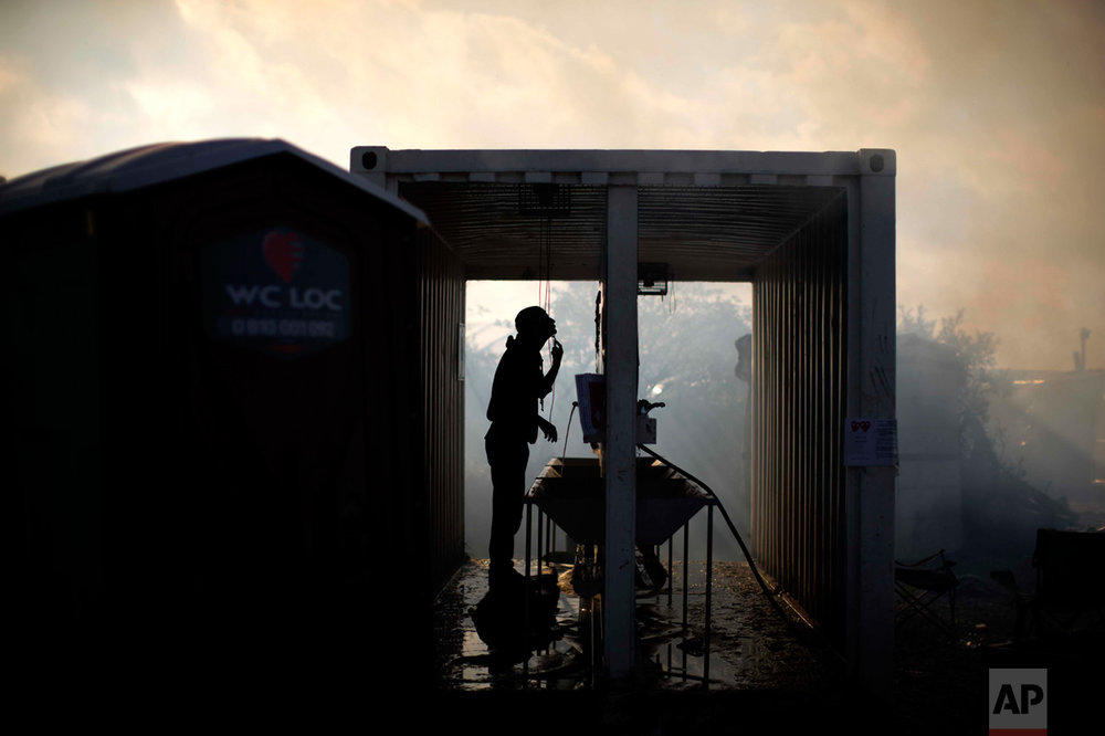 "In this Thursday, Oct. 27, 2016 photo, a migrant shaves himself amid of smoke provoked by tents burning as workers clean-up a makeshift migrant camp known as ""the jungle"" near Calais, northern France. (AP Photo/Emilio Morenatti)"