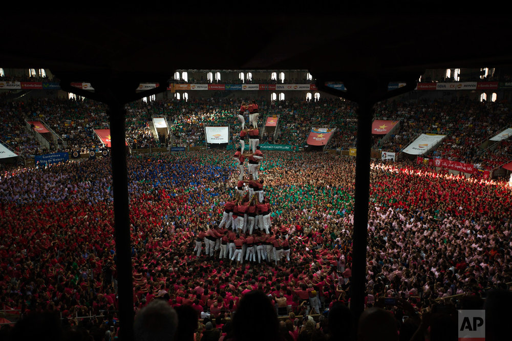 "In this Sunday, Oct. 2, 2016 photo, members of ""Vella de Xiquets de Valls"" try to complete their human tower during the 26th Human Tower Competition in Tarragona, Spain. The tradition of building human towers, or Castells, dates back to the 18th century and takes place during festivals in Catalonia, where ""colles"", or teams, compete to build the tallest and most complicated towers. (AP Photo/Emilio Morenatti)"