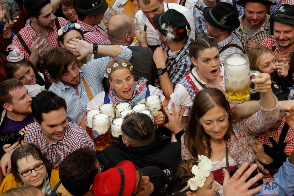 In this Saturday, Sept. 17, 2016 photo, a waitress is surrounded by visitors during the opening ceremony of the 183rd Oktoberfest beer festival in Munich, southern Germany. (AP Photo/Matthias Schrader)