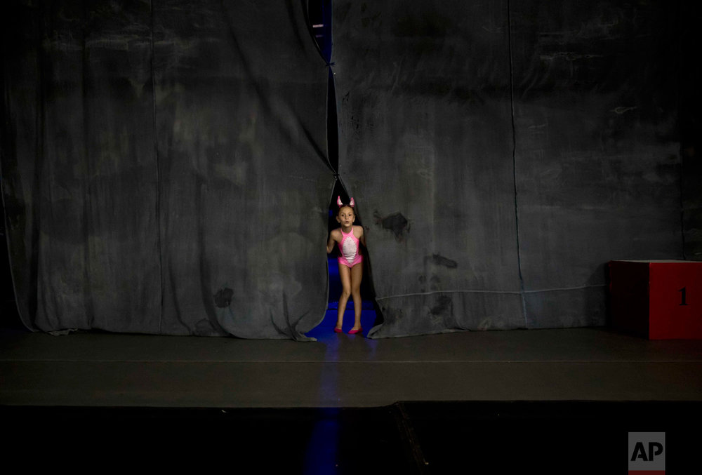 In this Sept. 10, 2016 photo, Diana Romaniuc, 7-years-old, peers from behind curtains before competing in the children category of the Romania Miss Pole Dance Contest, ahead of the finals of the Pole Sport&Fitness World Championship 2016 in Bucharest, Romania. (AP Photo/Vadim Ghirda)
