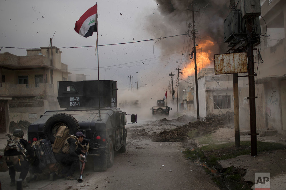 A car bomb explodes next to Iraqi special forces armored vehicles as they advance toward Islamic State-held territory in Mosul, Iraq, Wednesday, Nov. 16, 2016. Troops have established a foothold in the city's east from where they are driving northward into the Tahrir neighborhood. The families in Tahrir are leaving their homes to flee the fighting. (AP Photo/Felipe Dana)