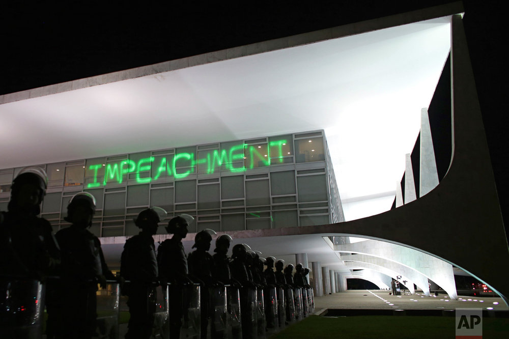 "In this March 21, 2016 photo, soldiers stand guard outside the Planalto presidential palace where protesters have projected the word ""Impeachment"" on the building, as they call for the impeachment of Brazil's President Dilma Rousseff, in Brasilia, Brazil. About six months later senators voted to impeach and remove Rousseff, Brazil's first female president, from office. (AP Photo/Eraldo Peres)"