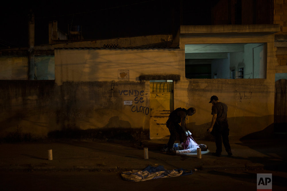In this July 16, 2016 photo, police responding to a call find the body of a young black man in the middle of a residential street in Caxias, greater Rio de Janeiro, Brazil. Rio's ambitious security push to bring crime down and seize control of certain slums ahead of the 2016 Summer Games crumbled. Overall slayings increased in 2016, the victims overwhelmingly young, black men. (AP Photo/Felipe Dana)