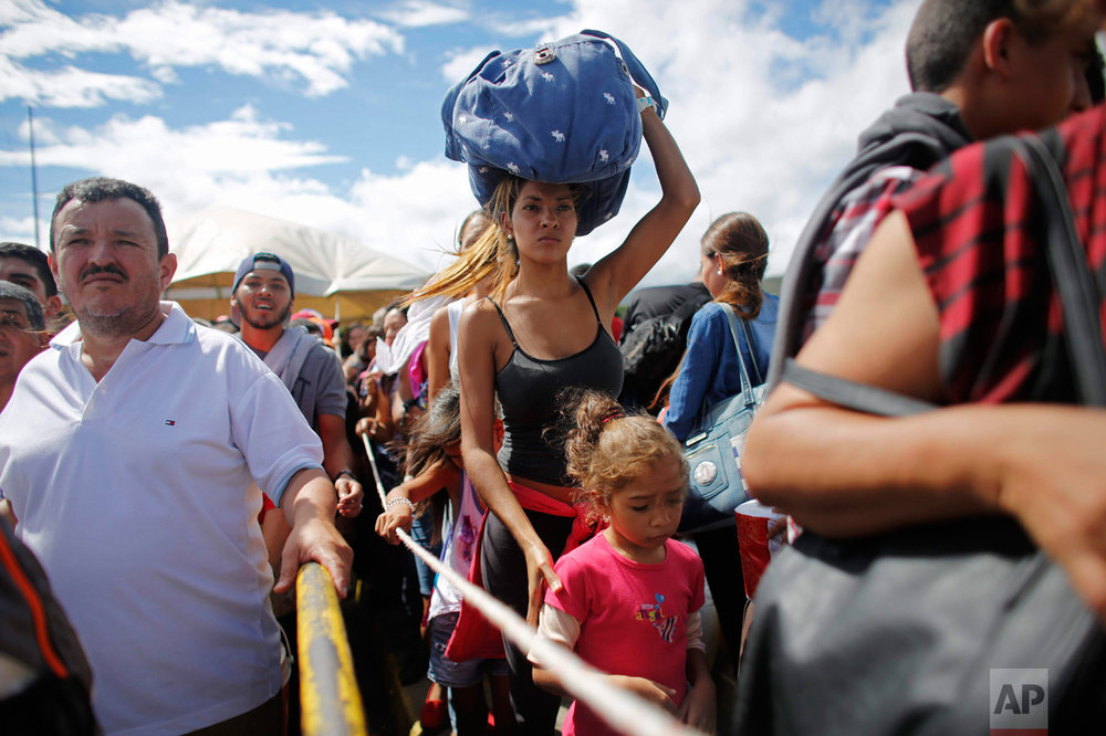 In this July 17, 2016 photo, a woman carrying a bundle on her head wait in line to cross the border into Colombia through the Simon Bolivar bridge in San Antonio del Tachira, Venezuela. In July tens of thousands of Venezuelans crossed the border into Colombia to hunt for food and medicine that are in short supply at home. It was the second weekend in a row that Venezuela's government opened the long-closed border with Colombia. (AP Photo/Ariana Cubillos)