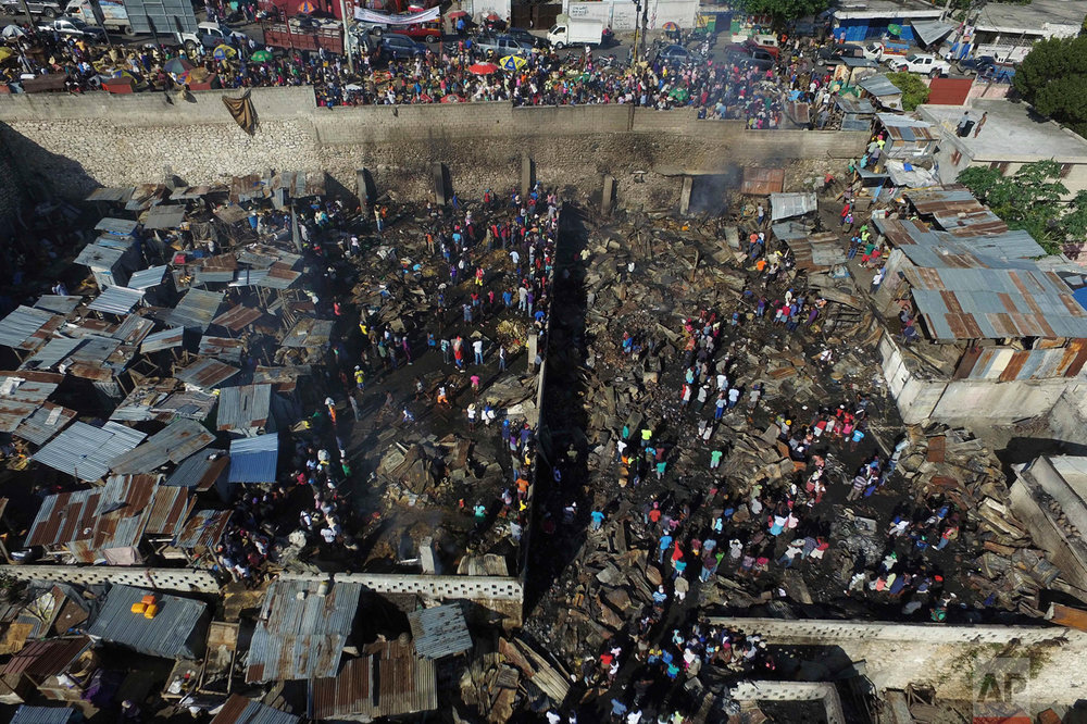 In this Nov. 21, 2016 photo, people walk through the charred remains of market shops gutted by an overnight fire in the Petion-Ville suburb of Port-au-Prince, Haiti. A major fire ripped through the central market in the hillside district above the capital. (AP Photo/Ricardo Arduengo)
