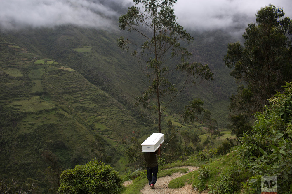 In this March 29, 2016 photo, a man shoulders a coffin with the remains of a loved one, who was slain more than two decades ago by Shining Path guerrillas, while walking to the cemetery for a mass burial service, in Huanta, Peru. The remains of 40 victims were returned to their loved ones in a ceremony supported by the International Red Cross. (AP Photo/Rodrigo Abd)