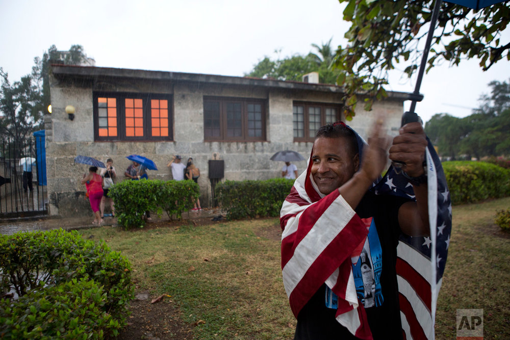 In this March 20, 2016 photo, a Cuban wearing a U.S. national flag applauds as President Barack Obama's convoy passes by in the rain along the Malecon into Old Havana, Cuba. Obama's trip to the island nation was a crowning moment in his and Cuban President Raul Castro's ambitious effort to restore normal relations between their countries. (AP Photo/Rebecca Blackwell)