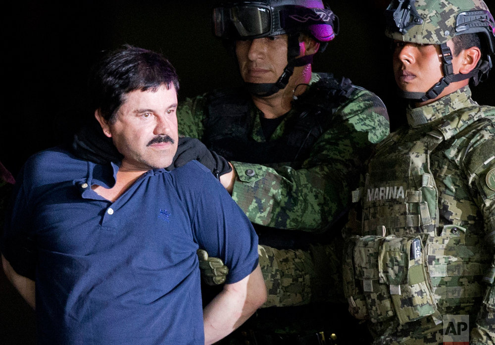 "In this Jan. 8, 2016 photo, a handcuffed Joaquin ""El Chapo"" Guzman is made to face the press as he is escorted to a helicopter by Mexican soldiers and marines at a federal hangar in Mexico City. Mexican President Enrique Pena Nieto announced Guzman was recaptured six months after escaping from a maximum security prison. (AP Photo/Eduardo Verdugo)"