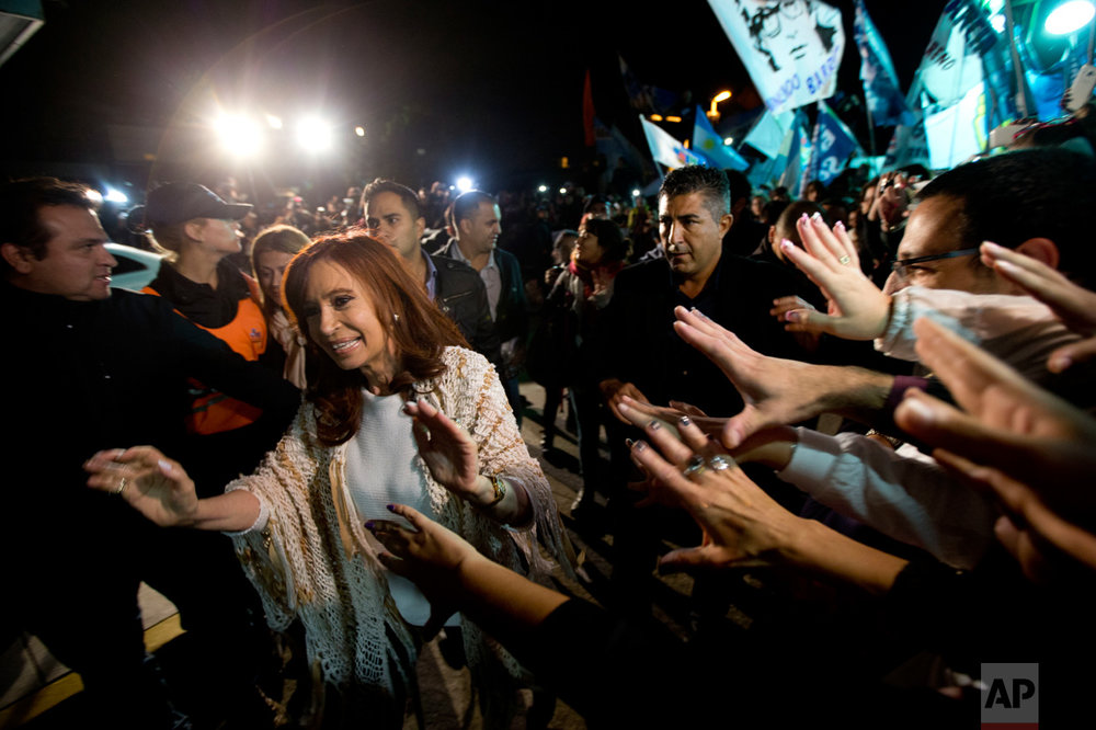 In this April 11, 2016 photo, Argentina's former President Cristina Fernandez, left, is greeted by followers upon her arrival at the airport in Buenos Aires, Argentina. After spending four months in Patagonia, Fernandez' supporters gave her a hero's welcome at a Buenos Aires airport before facing a court over her possible role in an alleged scheme to manipulate the country's currency. (AP Photo/Natacha Pisarenko)