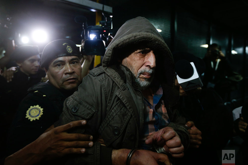 In this Jan. 12, 2016 photo, a handcuffed Brayan Jimenez, the former president of the Guatemalan football federation, is escorted by police into a courthouse in Guatemala City. Jimenez has been a fugitive for a month after Guatemala issued warrants for his arrest. Jimenez allegedly took a bribe to sell television rights to the 2018 World Cup qualifying matches. (AP Photo/Arnulfo Franco)