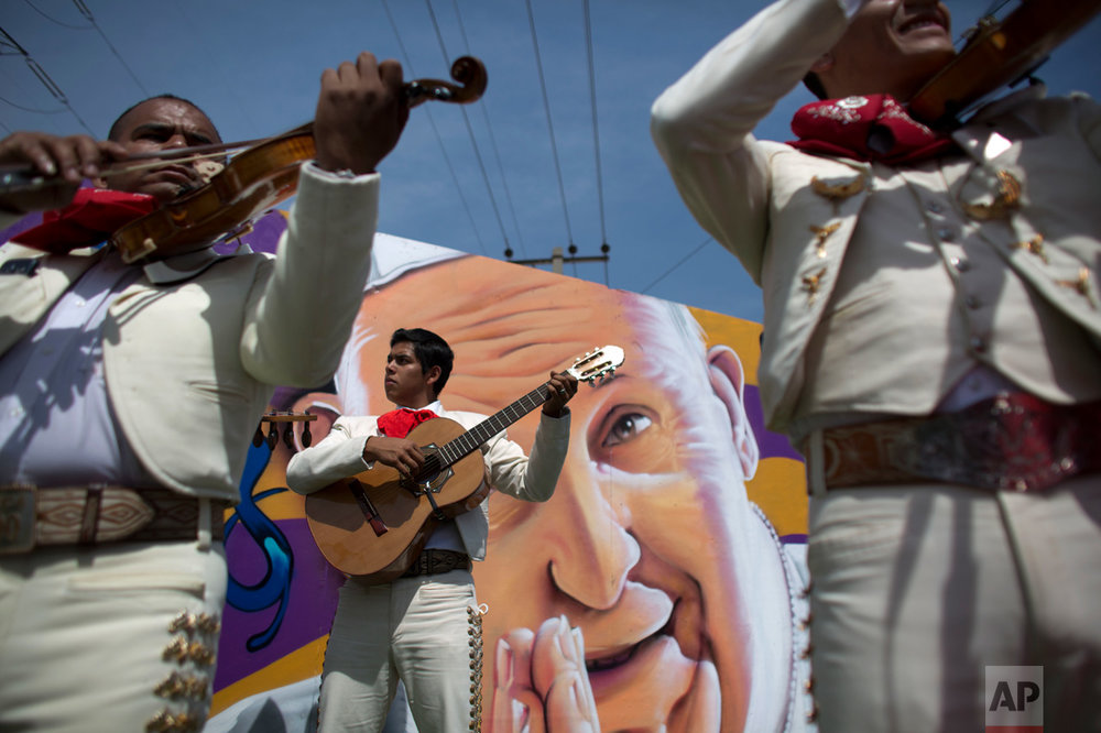 "In this Feb. 14, 2016 photo, mariachis backdropped by a mural depicting Pope Francis, as they wait for the popemobile to pass following the end of a Mass, in Ecatepec, Mexico. Francis condemned the drug trade's ""dealers of death"" and urged Mexicans to shun the devil's lust for money at the huge open-air Sunday Mass for more than 300,000 people in this violence-riddled city. (AP Photo/Rebecca Blackwell)"