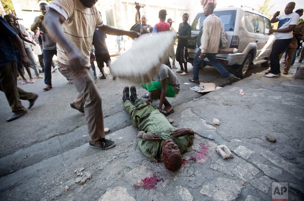 In this Feb. 5, 2016 photo, an anti-government protester drops a large cinderblock on the head of Neroce R. Ciceron, in Port-au-Prince, Haiti. A former captain of Haiti's disbanded army, Ciceron was beaten to death during a clash between members of the abolished military and protesters who were demanding the resignation of Haiti's President Michel Martelly. (AP Photo/Dieu Nalio Chery)