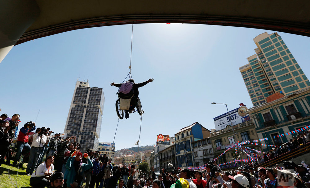 In this May 3, 2016 photo, a woman in a wheelchair hangs from a rope under a footbridge during a demonstration demanding better state benefits and equal rights for people with disabilities, in downtown La Paz, Bolivia. People protested for almost two months but to no avail. Many who had traveled from the countryside returned home empty-handed. (AP Photo/Juan Karita)