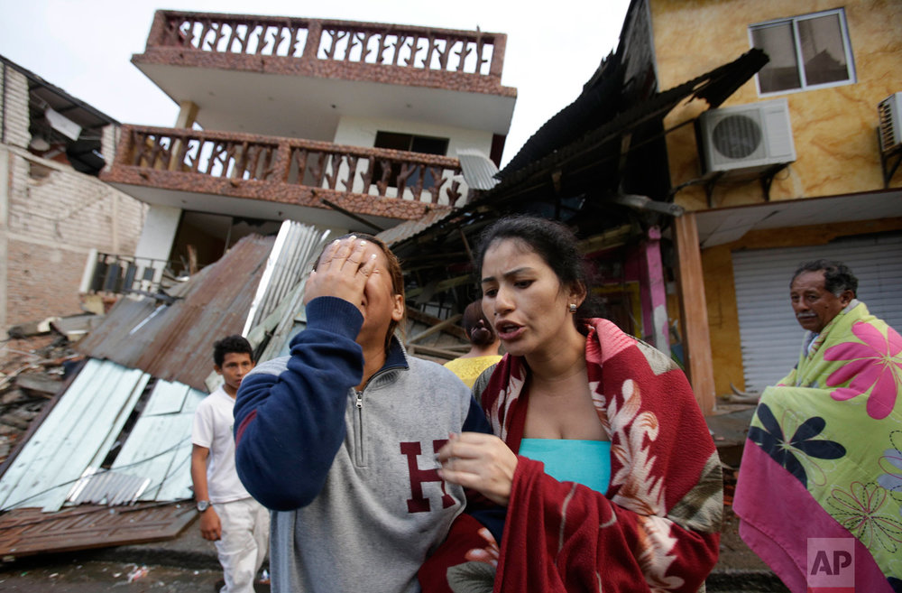In this April 17, 2016 photo, a woman cries as she stands next to a house destroyed by the earthquake in the Pacific coastal town of Pedernales, Ecuador. The strongest earthquake to hit Ecuador in decades flattened buildings and buckled highways along its Pacific coast, sending the Andean nation into a state of emergency. (AP Photo/Dolores Ochoa)