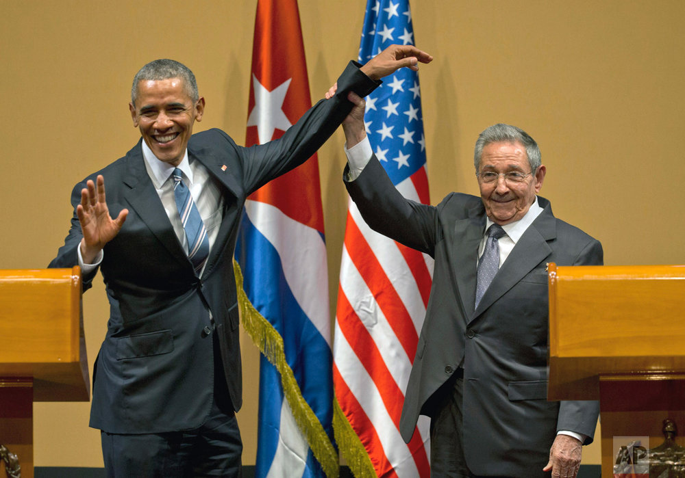 In this March 21, 2016 photo, Cuban President Raul Castro, right, lifts up the arm of President Barack Obama, at the conclusion of their joint news conference at the Palace of the Revolution, in Havana, Cuba. Obama was joined by wife Michelle Obama and daughters Malia and Sasha in the first visit by a sitting president to the island nation in 88 years. (AP Photo/Ramon Espinosa)