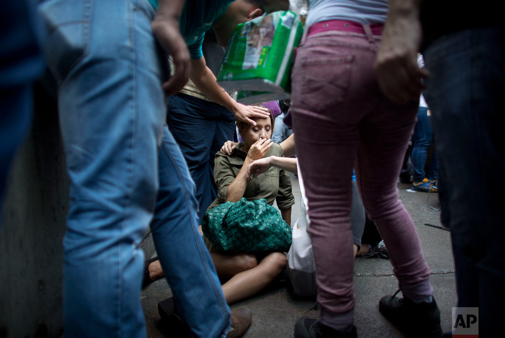 In this May 5, 2016 photo, Irama Carrero is aided by fellow shoppers after fainting in a food line outside a grocery store, in Caracas, Venezuela. Carrero, who said she hadn't eaten that day, had spent hours staring blankly ahead in the line for the elderly when her gaze suddenly became more fixed. She tilted backward and no one broke her fall. Her head smacked the concrete and when she came to she started vomiting. (AP Photo/Ariana Cubillos)