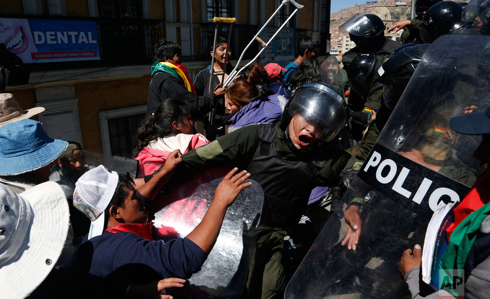 In this May 3, 2016 photo, protesters push against police who eventually failed to block them from reaching a footbridge where they planned a demonstration in downtown La Paz, Bolivia. The demonstration called attention to the group's demand for an increase in state benefits for those with disabilities. (AP Photo/Juan Karita)