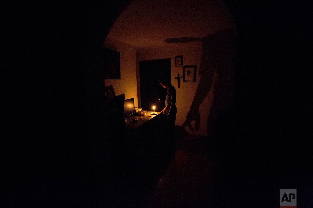 In this April 23, 2016 photo, a boy illuminates his home with a candle during a 24-hour blackout, in the El Calvario neighborhood of El Hatillo, just outside of Caracas, Venezuela. Energy rationing was added to the hardships faced by Venezuelans overwhelmed by inflation, shortages of food and medicine, and rising crime. (AP Photo/Fernando Llano)