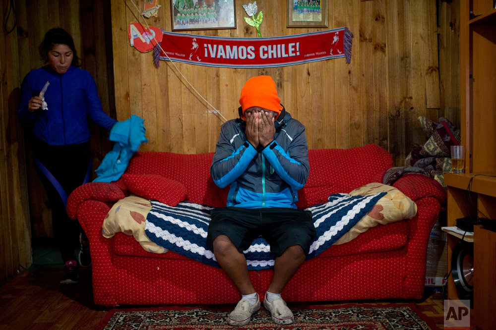 "In this May 10, 2016 photo, diver Jose Luis Cifuentes covers his face in exhaustion and frustration inside his mother-in-law's home, saying he has no money to buy food, in Ancud, Chiloe Island, Chile, as the country faced its worst ever ""red tide"" environmental disaster, threatening the livelihoods of the local fishermen. The government declared an emergency zone along the southern coast that encompasses these islands known known for its dramatic landscapes, rich wildlife, quaint stilt homes and colonial-era churches. (AP Photo/Esteban Felix)"