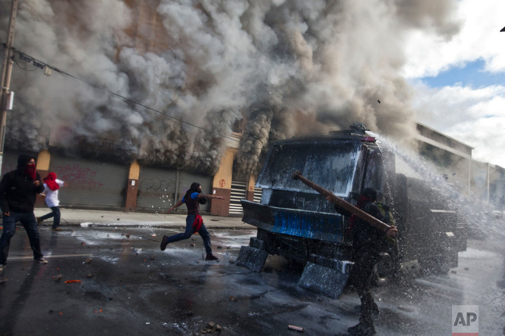 In this May 21, 2016 photo, masked protesters attack a police water canon in front of a burning pharmacy near Congress where President Michelle Bachelet was presenting the state-of-the-nation report, in Valparaiso, Chile. The anti-government protest began as a peaceful march but turned rough as some demonstrators threw rocks at police and gasoline bombs at buildings, resulting in the death of one man who reportedly died of asphyxiation. (AP Photo/Esteban Felix)
