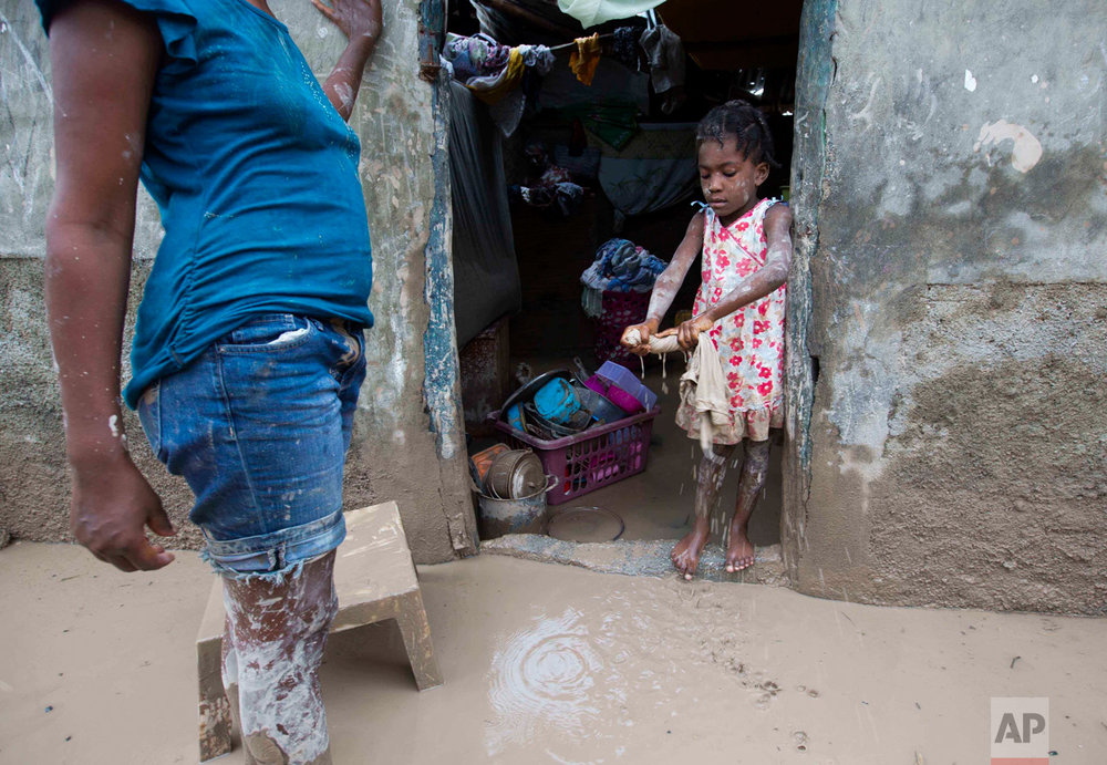 In this Oct. 6, 2016 photo, a girl helps her mother to remove mud after Hurricane Matthew flooded their home in Les Cayes, Haiti. Haitian and international agricultural officials said it could be a decade or more before the southwestern peninsula recovers economically from Hurricane Matthew, which struck hard at the rugged region of more than 1 million people that is almost completely dependent on farming and fishing. (AP Photo/Dieu Nalio Chery)