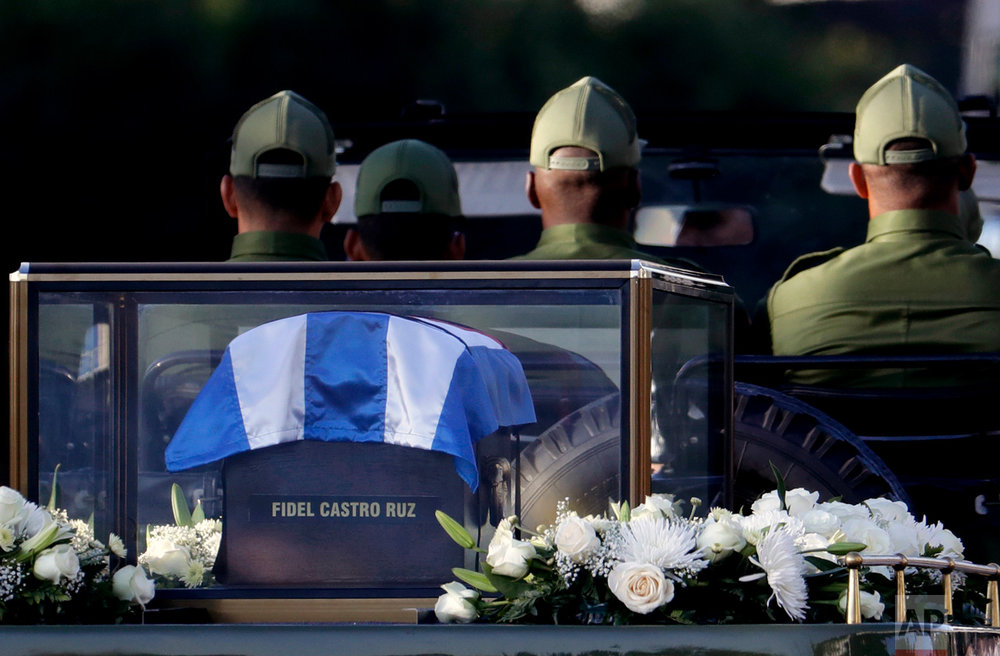 This Nov. 30, 2016 photo shows a flag-draped cedar coffin containing the remains of the late Cuban leader Fidel Castro driven through the streets of Havana, Cuba. Castro's ashes made a four-day journey across Cuba from Havana to their final resting place in the eastern city of Santiago, to retrace in reverse his triumphant march into Havana nearly six decades ago. (AP Photo/Natacha Pisarenko)