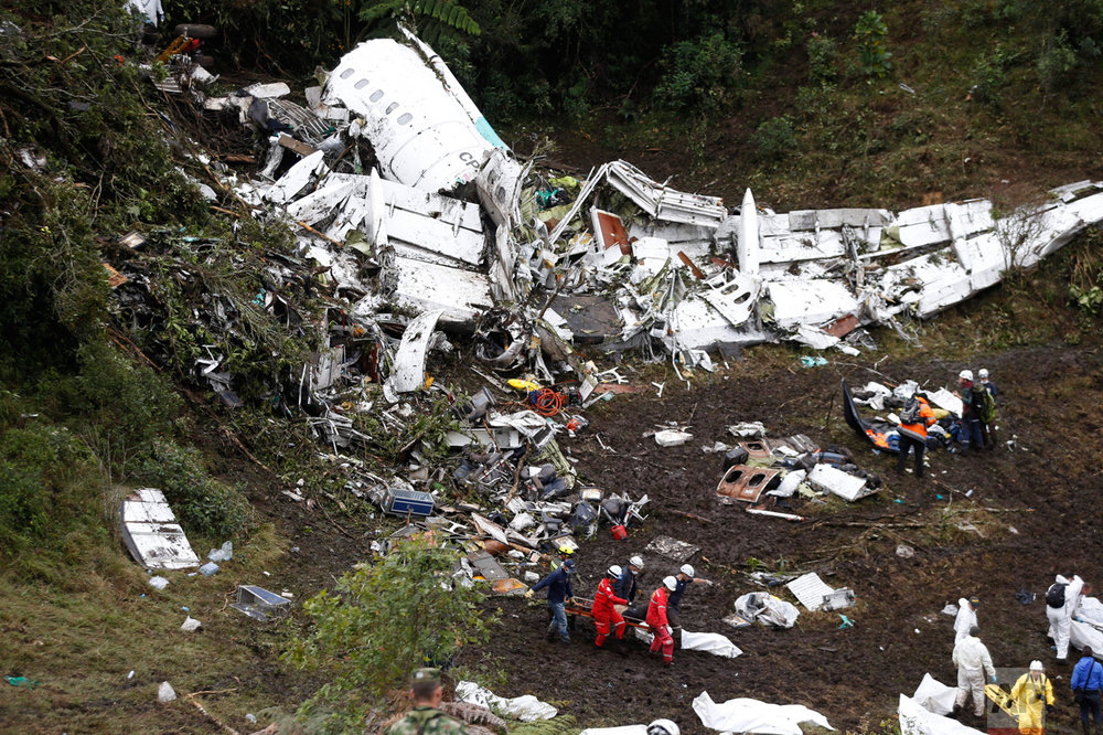 In this Nov. 29, 2016 photo, rescue workers recover a body from the wreckage site of an airplane crash, in La Union, a mountainous area near Medellin, Colombia. A LaMia jet carrying 77 people slammed into the Colombian mountainside just minutes after the pilot reported running out of fuel. The crash killed 71 of 77 aboard, including members of Brazil's Chapecoense soccer team and a group of journalists who were traveling to the Copa Sudamericana finals. (AP Photo/Fernando Vergara)