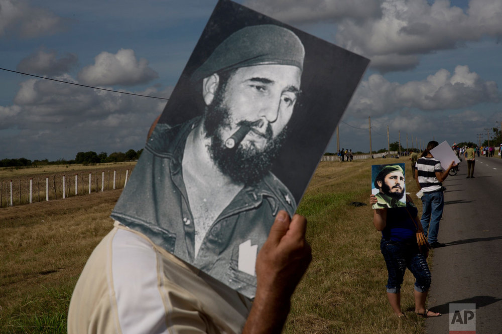 In this Dec. 2, 2016 photo, a man uses an image of Fidel Castro to shade himself from the sun while waiting for the convoy carrying the ashes of Cuba's late leader, along the central road near Yarigua, Las Tunas, Cuba. The convoy traced in reverse the victory tour Castro and his bearded rebels took after overthrowing the forces of strongman Fulgencio Batista in 1959, to his final resting place in the eastern city of Santiago. (AP Photo/Rodrigo Abd)