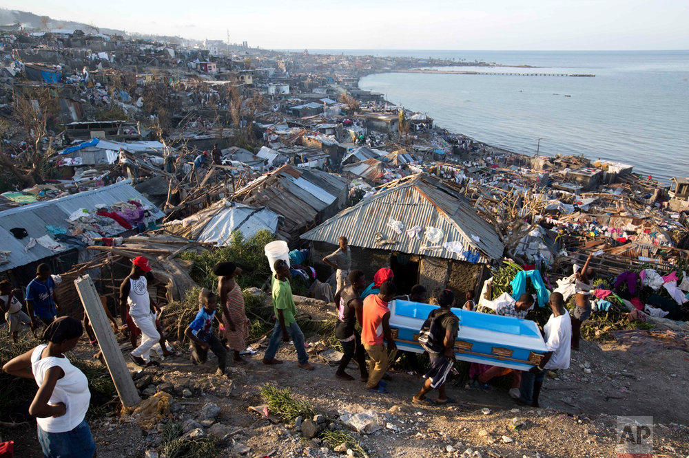 In this Oct. 7, 2016 photo, residents carry a coffin containing the remains of a pregnant woman, a victim of Hurricane Matthew, in Jeremie, Haiti. People across southwest Haiti dug through the wreckage of their homes, salvaging what they could of their meager possessions after Matthew killed hundreds of people in the impoverished country. (AP Photo/Dieu Nalio Chery)