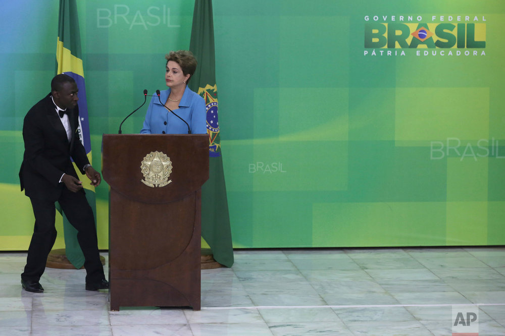 In this April 18, 2016 photo, a waiter walks in to serve water to Brazil's President Dilma Rousseff during a press conference where she spoke about her impeachment process, at Planalto Presidential Palace, in Brasilia. Rousseff, Brazil's first female president, was removed from office in September after a grueling impeachment trial that ended 13 years of the Workers' Party rule. (AP Photo/Eraldo Peres)
