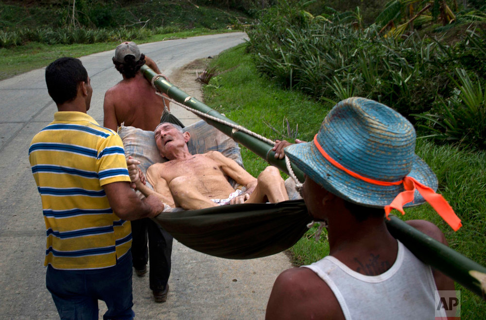 In this Oct. 6, 2016 photo, an elderly man, who was in a hospital before Hurricane Matthew hit, is carried home on a hammock in Baracoa, Cuba. He was carried back on foot because the roads were impassible due to damage caused by the storm, blocking all motor vehicle traffic to the area. (AP Photo/Ramon Espinosa)