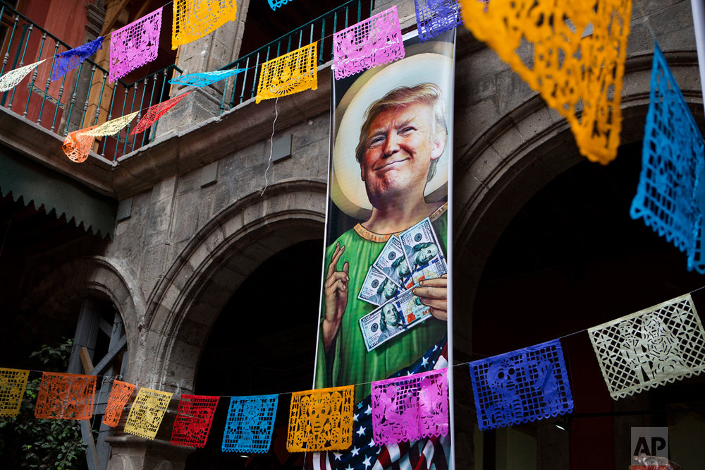 "In this Nov. 10, 2016 photo, a banner with an image of Donald Trump promotes an exhibition titled; ""Trump: A wall of caricatures,"" surrounded by intricately-cut tissue paper known as papel picado, inside the Caricature Museum in downtown Mexico City. The exhibition, which featured dozens of works by Mexican and international cartoonists, mocked amongst other things the president-elect's derogatory statements about Mexicans and his plans to build a wall between the two countries. (AP Photo/Rebecca Blackwell)"