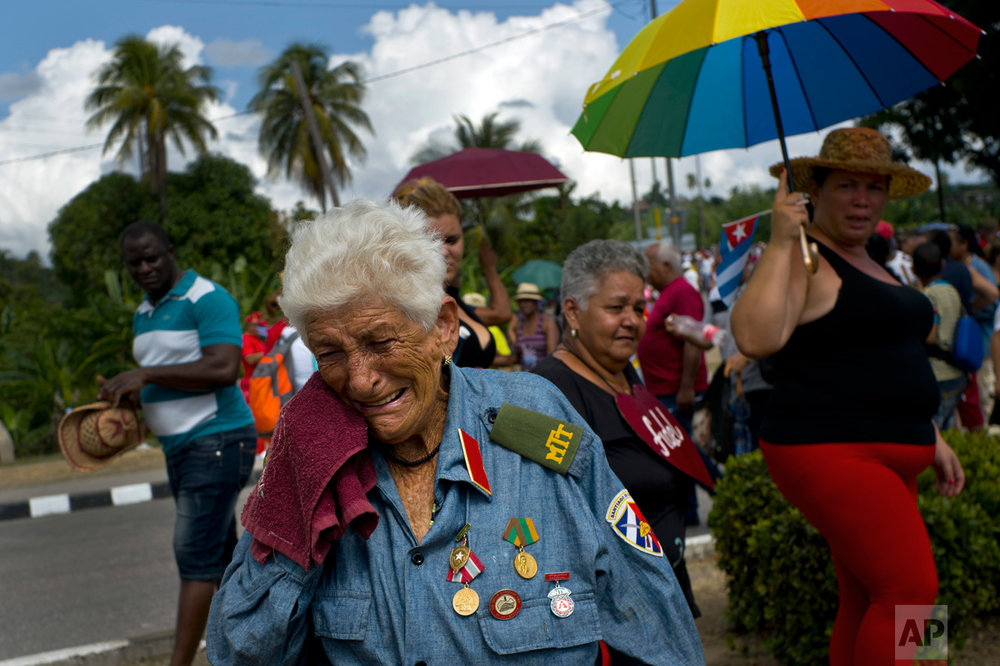 In this Dec. 3, 2016 photo, a former combatant of the Revolutionary Army, Paulina Ballard, 81, weeps after watching the funeral procession carrying the ashes of Cuba's late leader Fidel Castro, in Santiago, Cuba. The ashes were interred Dec. 4, ending the nine-day mourning period for the man who ruled the country for nearly 50 years. (AP Photo/Ramon Espinosa)