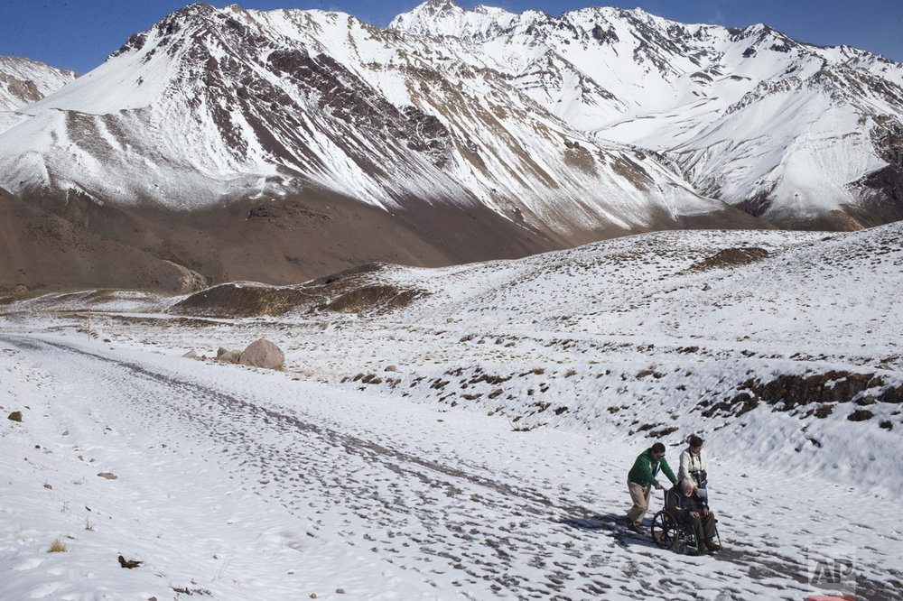 In this May 3, 2016 photo, Mariano Arias pushes Joshep Sumer's wheelchair, accompanied by Sumer's wife Marie Claire, during a visit to the Aconcagua National park in Las Heras, Argentina. The Belgium couple came to the park to see the Aconcagua, marked as the highest peak in the American continent. (AP Photo/Esteban Felix)