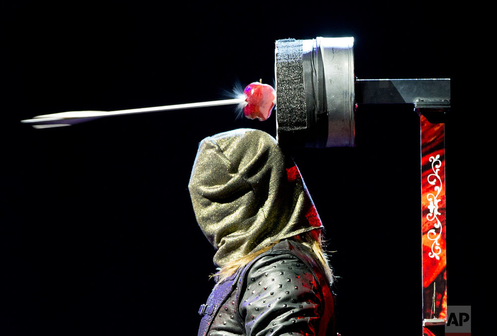 "In this July 13, 2016 photo, Ben Blaque, a crossbow sharpshooter, stands still after firing a crossbow wearing a hood, that then triggered a series of pre-set crossbows culminating in an arrow piercing the apple above his head, during media event to promote the magic show, The Illusionists 1903, at the National Auditorium in Mexico City. The Illusionists 1903, evoke the ""golden era"" of magic shows. (AP Photo/Rebecca Blackwell)"