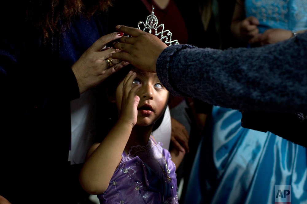 "In this Oct. 14, 2016 photo, Mariela Flores, who is visually impaired, is crowned one of two Miss ""Jacha Uru"", translated from the Aymaran language as Great Day, in La Paz, Bolivia. The families of people with disabilities, with the help of the city government, organized a pageant to promote the rights of children and adolescents with impairments that ranged from physical to sensory to developmental. About 50 contestants demonstrated their skills in singing or dancing, and wrapped up the competition sporting their finest evening wear. (AP Photo/Juan Karita)"
