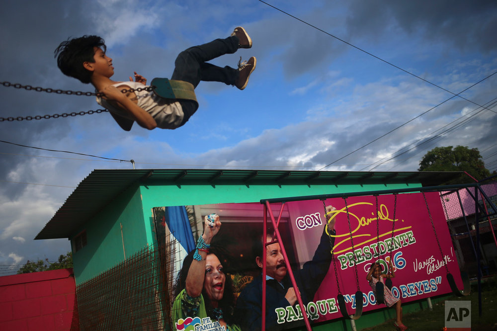 In this Friday, Nov. 4, 2016 photo, a boy swings in a park next to an election billboard promoting Nicaragua's President Daniel Ortega and his wife Rosario Murillo, in Managua, Nicaragua. Ortega was re-elected on Nov. 6, for his third consecutive term, this time accompanied by his wife as vice president. (AP Photo/Esteban Felix)