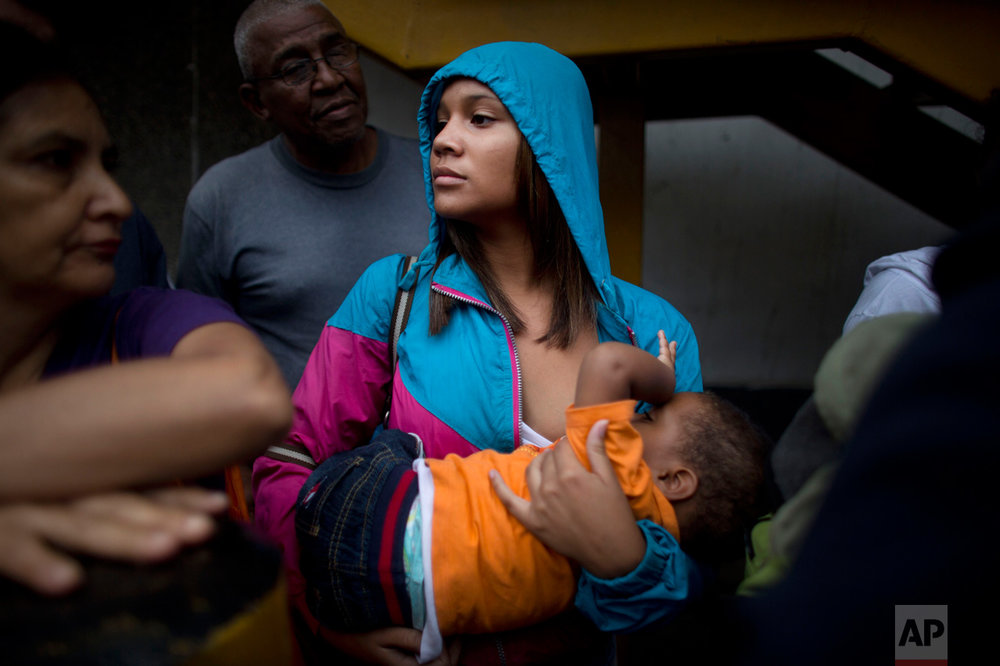 In this May 3, 2016 photo, 16-year-old Madeley Vasquez breastfeeds her one-year-old son Joangel as she waits in line outside a supermarket to buy food in Caracas, Venezuela. As Venezuela's lines grew longer and more dangerous, they became not only the stage for everyday life, but a backdrop to death. More than two dozen people have been killed in line in the past 12 months, including a 4-year-old girl caught in gang crossfire. Vasquez once ran down the block to avoid getting caught up in a knife fight that broke out when a woman was accused of cutting the line. (AP Photo/Ariana Cubillos)