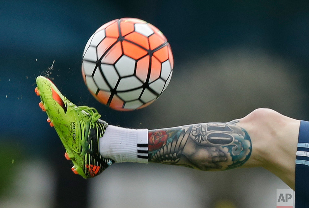 In this March 21, 2016 photo, Argentina's Lionel Messi kicks the ball during a training session in Buenos Aires, Argentina. Argentina will face Chile on a World Cup qualifying soccer match in Santiago, Chile on March 24. (AP Photo/Natacha Pisarenko)
