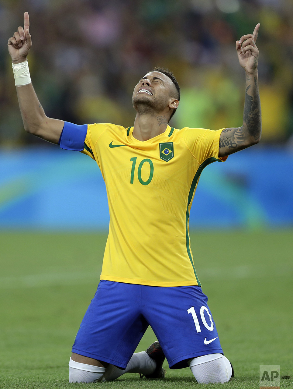 In this Aug. 20, 2016 photo, Brazil's Neymar weeps as he kneels down to celebrate after scoring the decisive penalty kick during the final match of the men's Olympic football tournament between Brazil and Germany at the Maracana stadium in Rio de Janeiro, Brazil. Brazil won the gold medal on a penalty shootout. (AP Photo/Andre Penner)