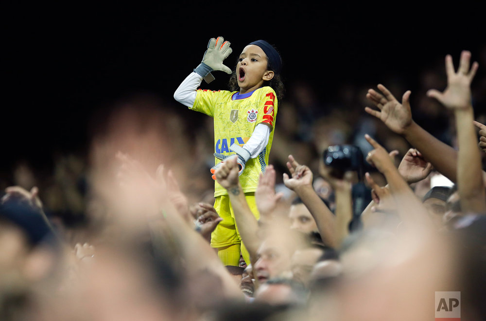 In this March 16, 2016 photo, a young fan of Brazil's Corinthians, dressed as the team's goalkeeper Cassio, cheers during a Copa Libertadores soccer match against Paraguay's Cerro Porteno in Sao Paulo, Brazil. (AP Photo/Andre Penner)